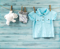 Baby boy t-shirt, socks and white toy bear on a clothesline Royalty Free Stock Photography