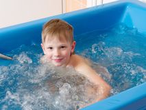 Baby boy is taking a bath with bubbles. Jacuzzi bubble bath procedure.  royalty free stock images