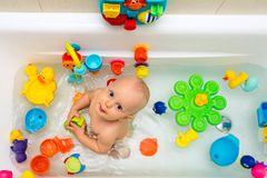 Baby boy taking a bath, playing with colorful toys Stock Photography