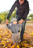 Baby boy taking first steps with father help Royalty Free Stock Images