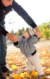 Baby boy taking first steps with father help Royalty Free Stock Photography