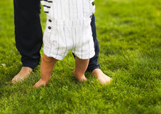 Baby boy taking first steps and mother helping Royalty Free Stock Images