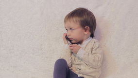 Baby boy talking on the phone stock footage
