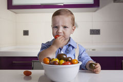 Baby boy tasting ripe colorful cherry tomatoe. Education on healthy nutrition for children concept Stock Photos