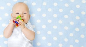 Baby Boy with Teether Toy In Mouth over Blue, Happy Infant Kid Boy in Bodysuit. Baby Boy with Teether Toy In Mouth over Blue Background, Happy Infant Kid Boy in stock photo