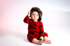 Baby Boy Tipping His Hat. A sly looking baby boy sits with a side tipped hat. He is looking off camera with a confident and slightly cocky look on his face. He Royalty Free Stock Photo