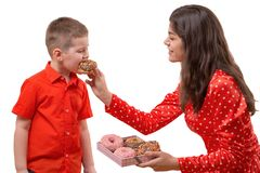 Baby boy toddler eat sweet donut. a woman is feeding a baby with a donut. Baby boy toddler eat sweet donut. a women is feeding a baby with a donut. isolate Royalty Free Stock Photography