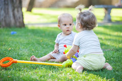 Baby boy and toddler girl playing while sitting on green grass Royalty Free Stock Photo