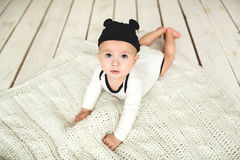 Baby boy in toddler and mouse hat on wooden floor
