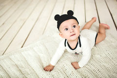 Baby boy in toddler and mouse hat on wooden floor Royalty Free Stock Photography