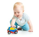 Baby boy toddler playing with toy car. Isolated Royalty Free Stock Photo