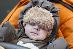Baby boy toddler sleeping in orange pram Royalty Free Stock Images