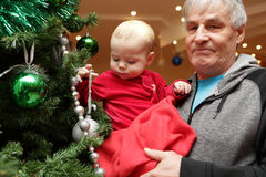 Baby boy touching christmas tree Royalty Free Stock Images