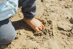 Baby boy touching the sand with his foot at the beach Stock Photo