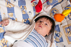 Baby boy with toys. Closeup of cute baby boy lying on comfortable blanket with toys Royalty Free Stock Image