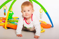 Baby boy with toys on mat Stock Image