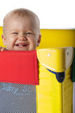 Baby Boy in Travelling Cot. Happy Baby Laughing in Colorful Travelling Cot Stock Photo