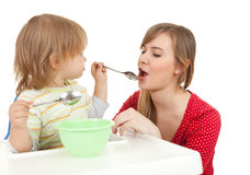 Baby boy trying feed young mother Stock Photo