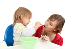 Baby boy trying feed young mother Stock Image