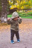 Baby boy trying to keep his balance. Being very happy and confident- he is in the park Stock Photography