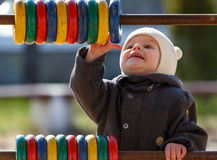 Baby boy trying to reach blue wooden circle outdoors Stock Photo