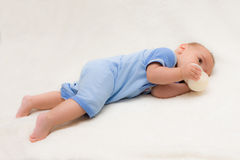 Baby boy on tummy drinking bottle Stock Photography