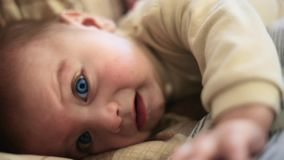 Baby boy turns in bed, lying, looking at the camera blue eyes. Can not find a comfortable position stock video