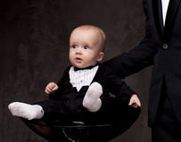 Baby boy in tuxedo on a chair Stock Image