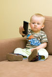 Baby boy with TV remote Stock Photo