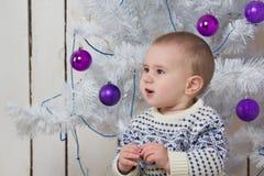 Baby boy under Christmas fir tree Stock Photos