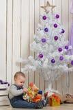 Baby boy under Christmas fir tree Royalty Free Stock Photos