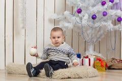 Baby boy under Christmas fir tree Stock Image