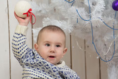 Baby boy under Christmas fir tree Stock Photo