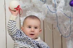 Baby boy under Christmas fir tree Stock Photo