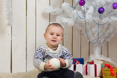 Baby boy under Christmas fir tree Royalty Free Stock Photo