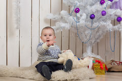 Baby boy under Christmas fir tree Stock Images