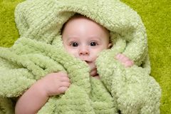 Baby boy under the green towel Royalty Free Stock Photography
