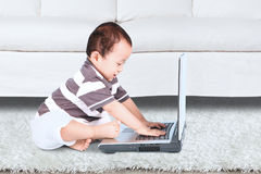 Baby boy using a notebook Stock Image