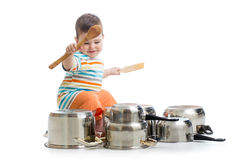 Baby boy using wooden spoons to bang pans drumset Royalty Free Stock Photos