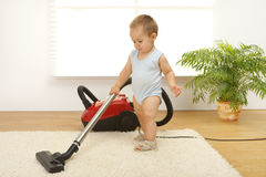 Baby boy with vacuum cleaner stock photo