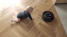 Kid versus Robot Vacuum Cleaner. Baby boy versus Robotic vacuum cleaner on wooden fioor view from above stock video footage