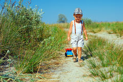Baby boy walking the field  path, dragging toy car Stock Photography