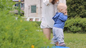 Baby boy walking in the park with mom's support stock footage