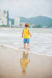 Baby boy walking on the sandy beach near the sea. Cute little kid at sand tropical beach. Royalty Free Stock Images
