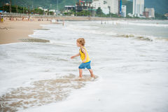Baby boy walking on the sandy beach near the sea. Cute little kid at sand tropical beach. Royalty Free Stock Photo