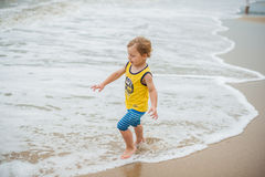 Baby boy walking on the sandy beach near the sea. Cute little kid at sand tropical beach. Stock Images