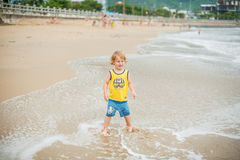 Baby boy walking on the sandy beach near the sea. Cute little kid at sand tropical beach. stock photography