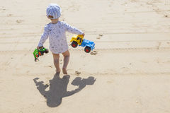 Baby boy walking with toys at the beach Royalty Free Stock Image
