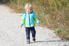 Baby boy walking through the village Stock Photo