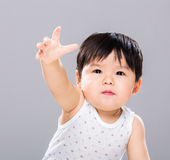 Baby boy want to get something in front. With gray background Royalty Free Stock Photos